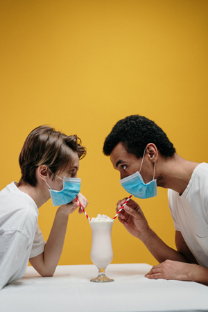man and woman in masks drinking milkshake