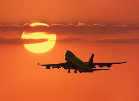 Plane flying towards sun
